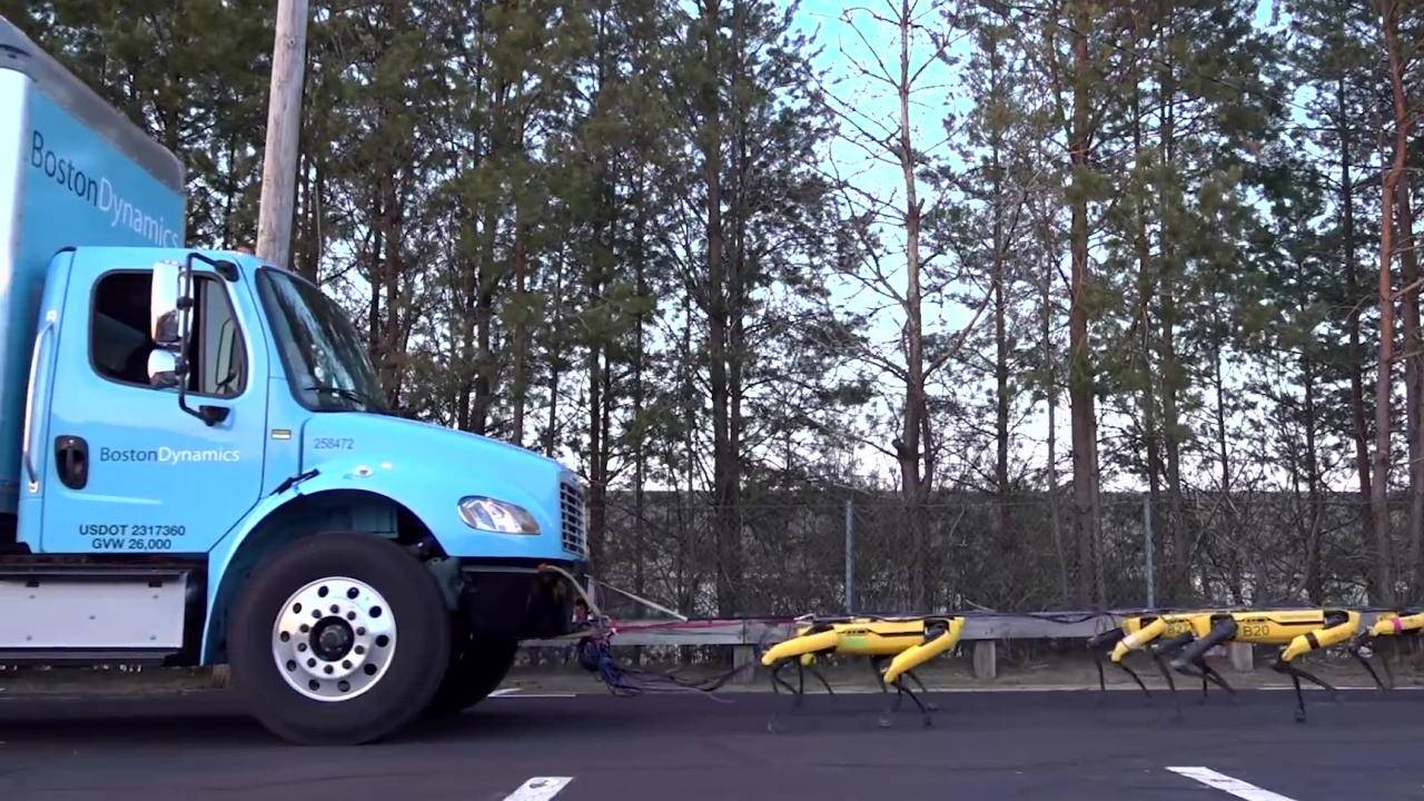 Boston Dynamics' SpotMini robots work together to pull a truck